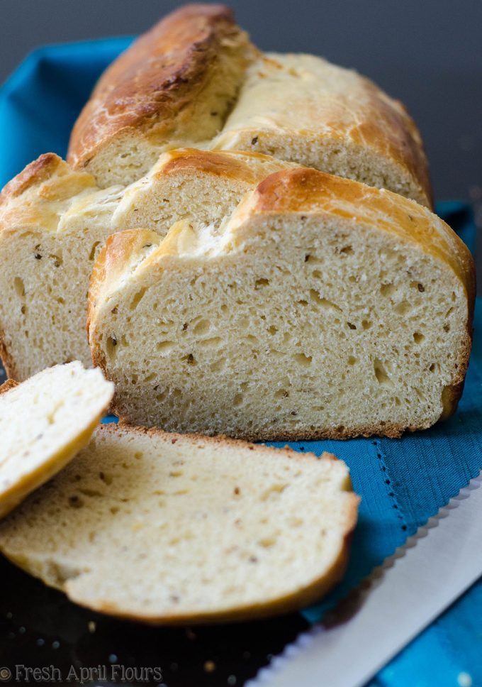 loaf of anise bread sliced and on a blue kitchen towel