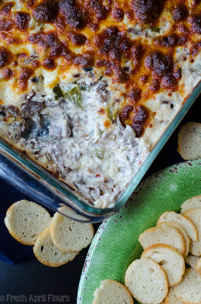 Philly Cheesesteak Dip: Creamy dip filled with flavorful onions, green pepper, mushrooms, and roast beef, topped with a crispy layer of provolone cheese.