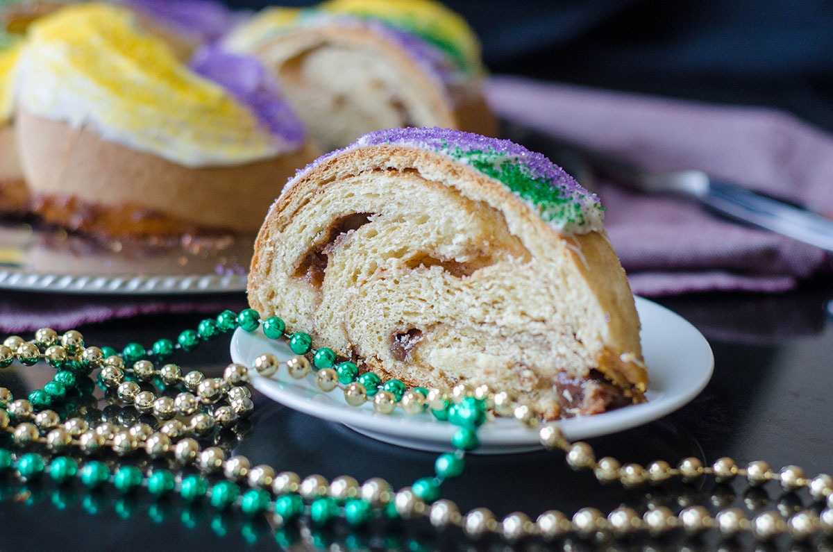mardi gras cake on a plate with beads around it