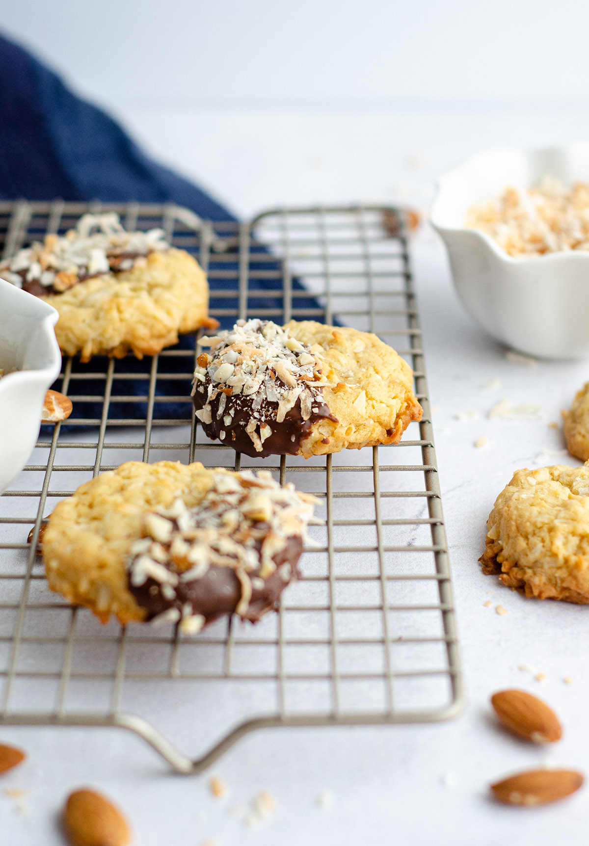 Easy coconut drop cookies, dipped in chocolate and sprinkled with toasted coconut and chopped almonds.