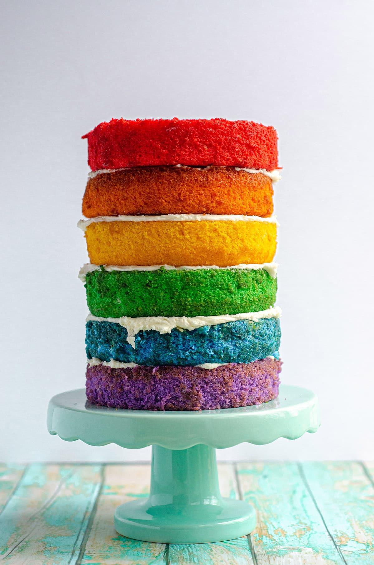 a naked rainbow cake on a cake stand