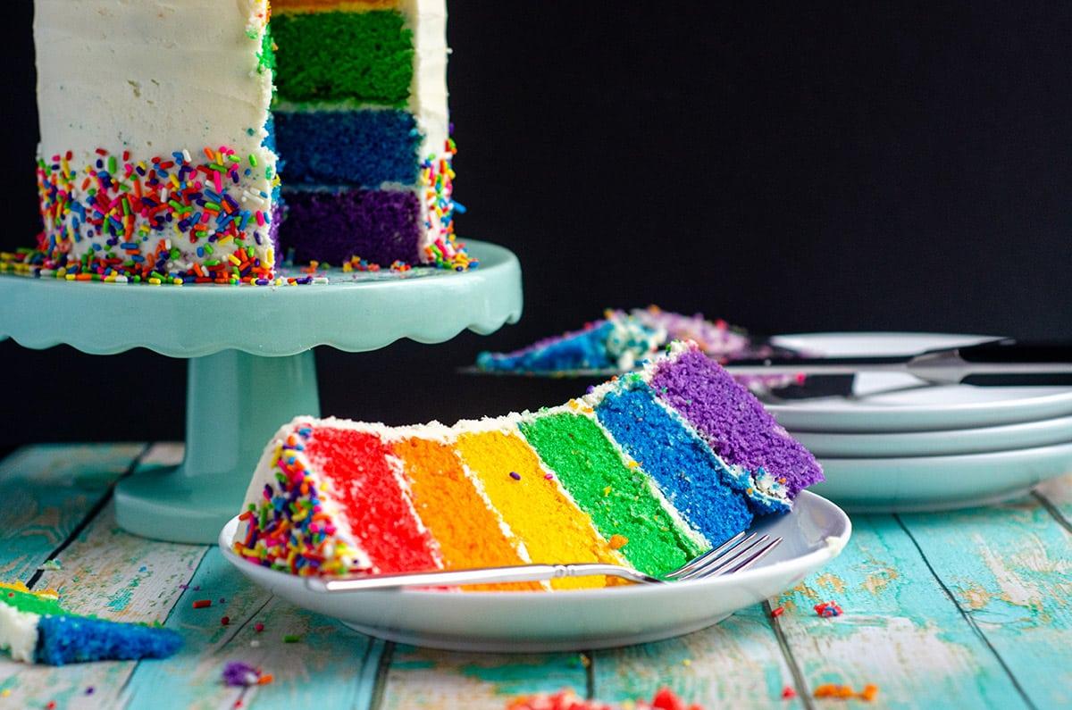 a slice of rainbow cake on a plate