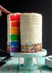 hand pulling a slice of rainbow cake out of the whole cake on a cake stand
