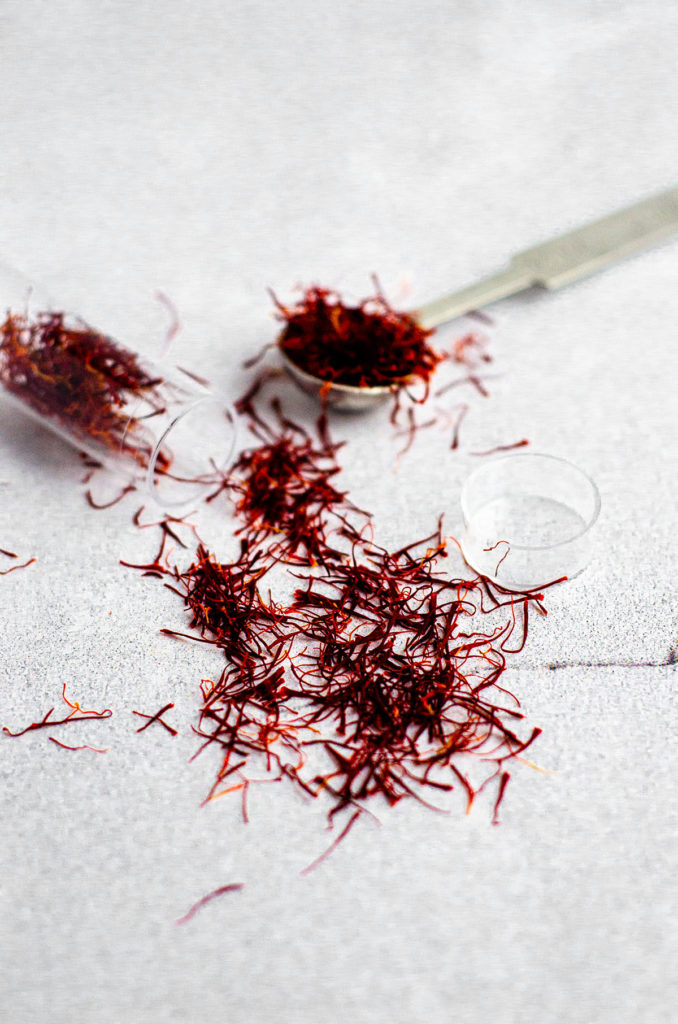 saffron spilling out of vial and some in measuring spoon