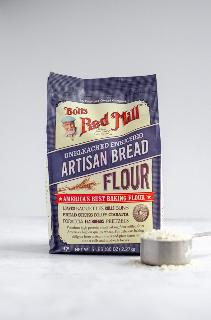 Bob's Red Mill Artisan Bread Flour bag with measuring cup full of flour