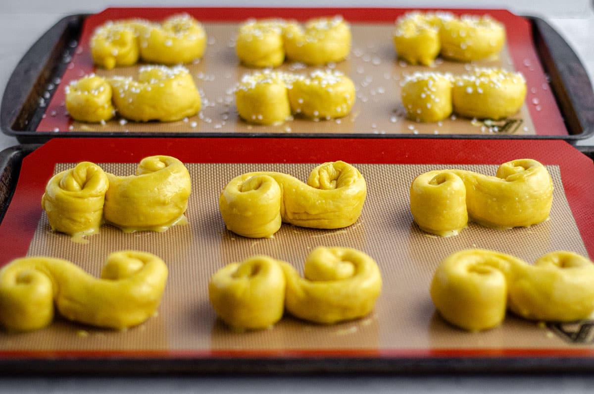 shaped saffron buns on a baking sheet