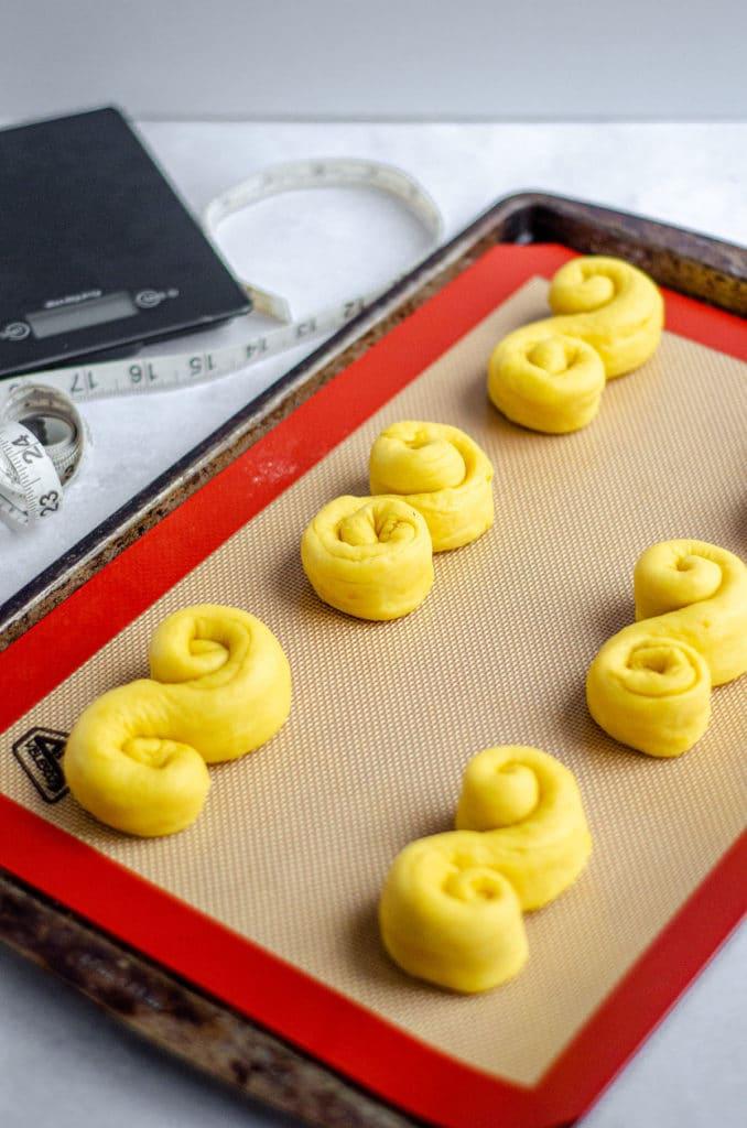 yellow saffron buns shaped into S shape ready to rise on baking sheet