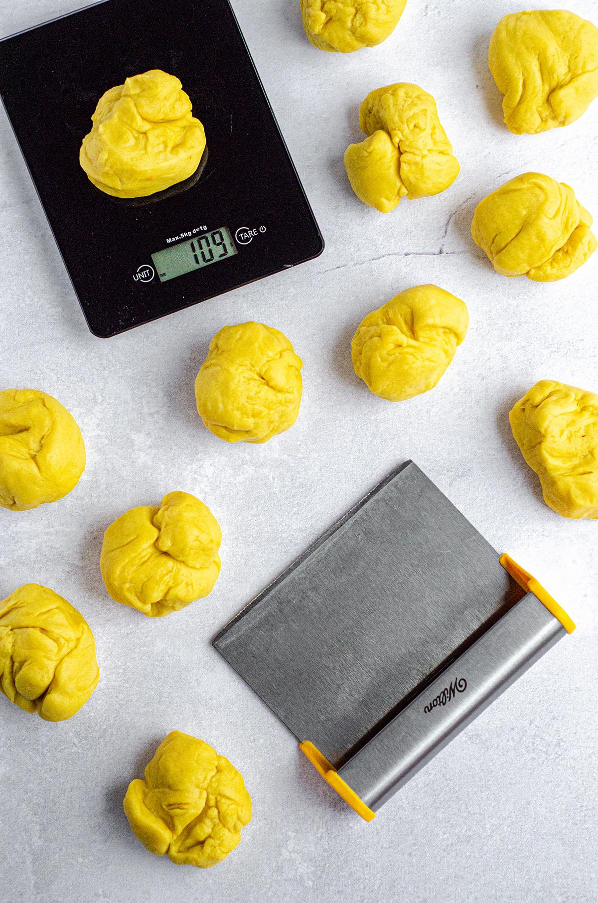 aerial photo of pieces of saffron bun dough prepared to form into bun shapes