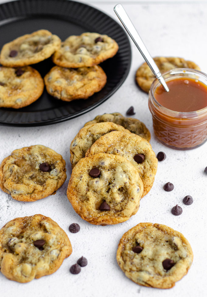 scattered cookies with a spoon in a jar of caramel sauce