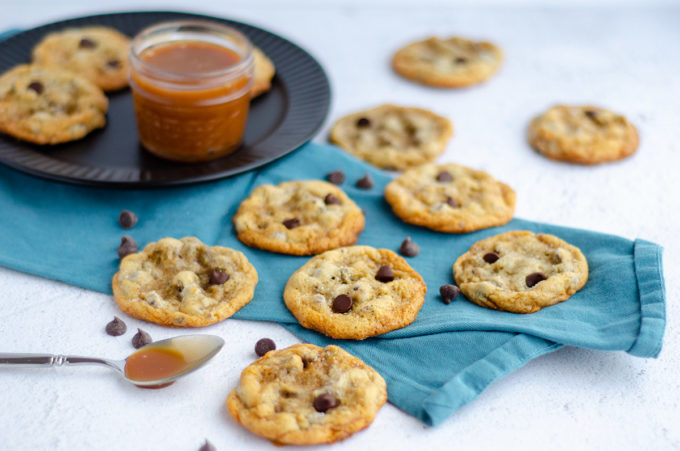 scattered cookies on a turquoise towel and a jar of caramel sauce on a black plate