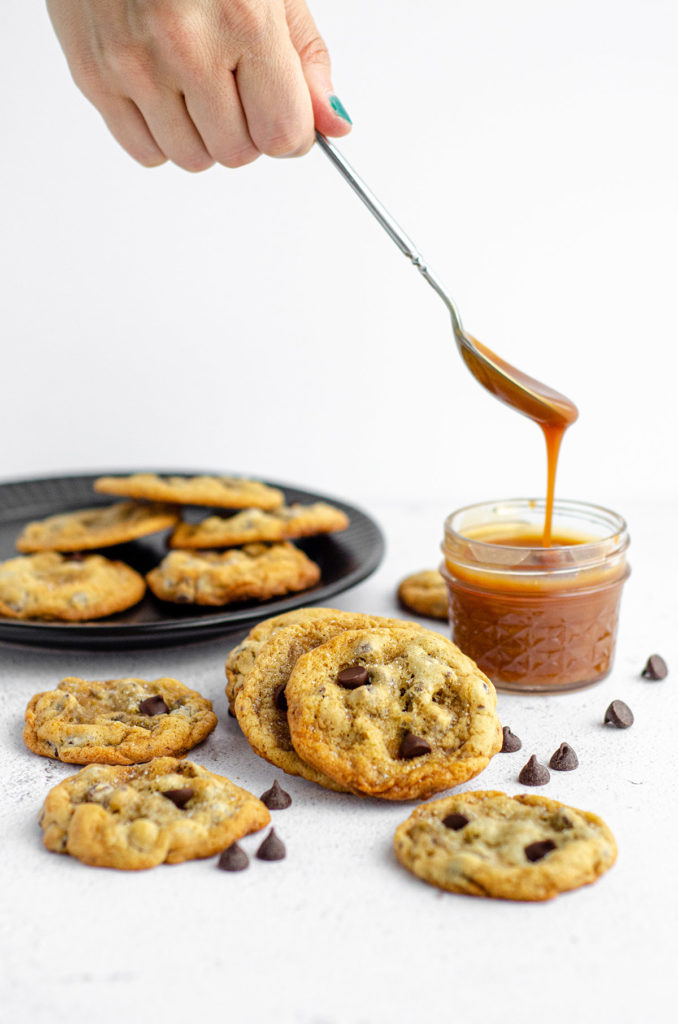 scattered cookies with a spoon dipping into a jar of caramel sauce
