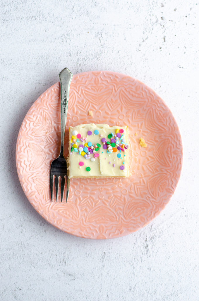 aerial shot of white sheet cake slice on a pink plate with a forkSimple White Sheet Cake: A perfectly moist and simple white cake that pairs with any frosting you prefer.