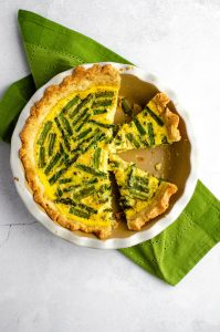 aerial photo of asparagus quiche in a pie plate sliced and ready to serve