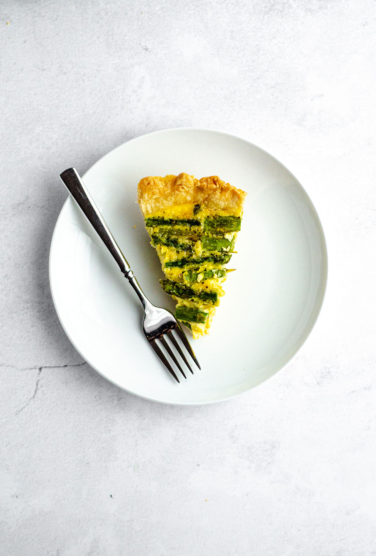 aerial photo of a slice of asparagus quiche on a plate with a fork