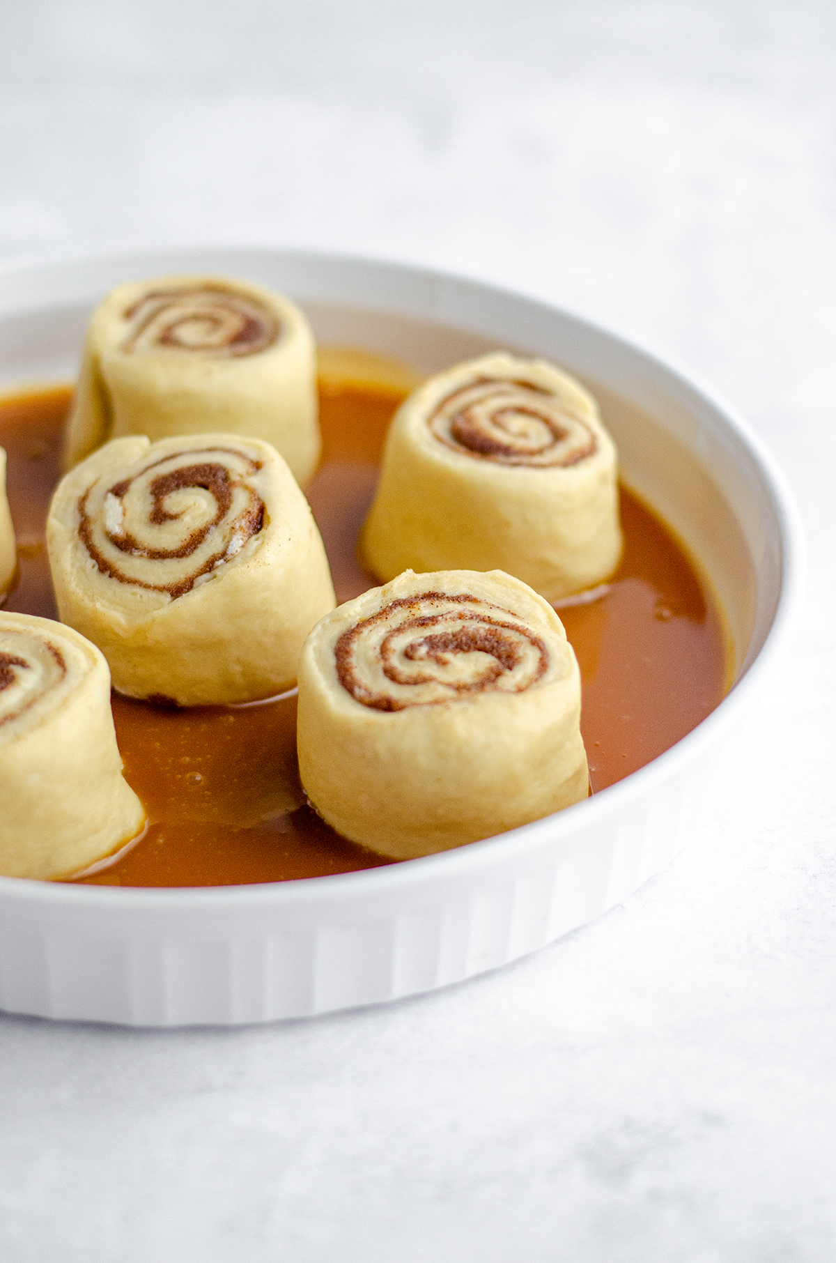 caramel roll dough in a plate with caramel sauce on the bottom ready to rise