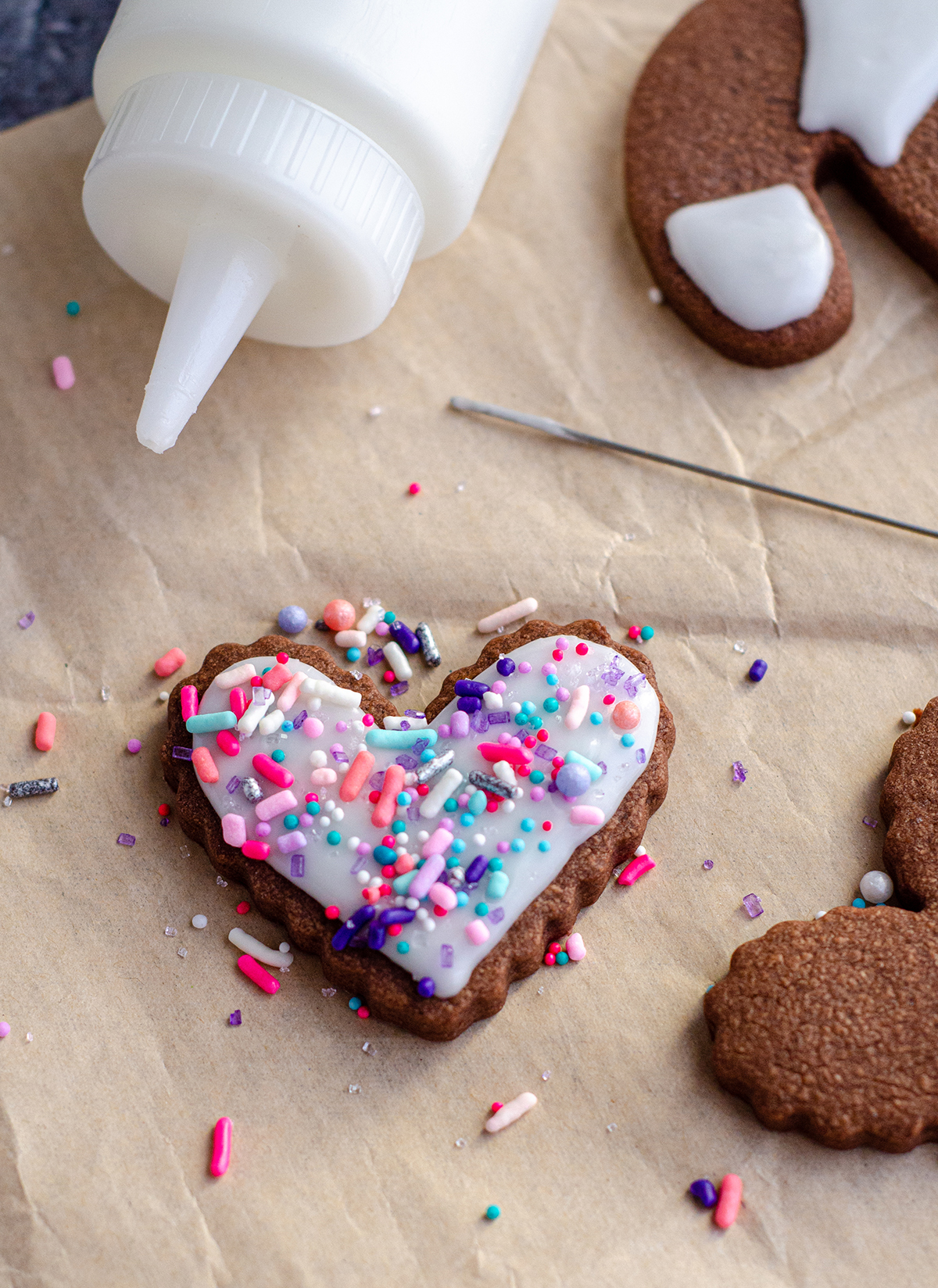 chocolate heart sugar cookie decorated with white royal icing and pink, purple, and blue sprinkles