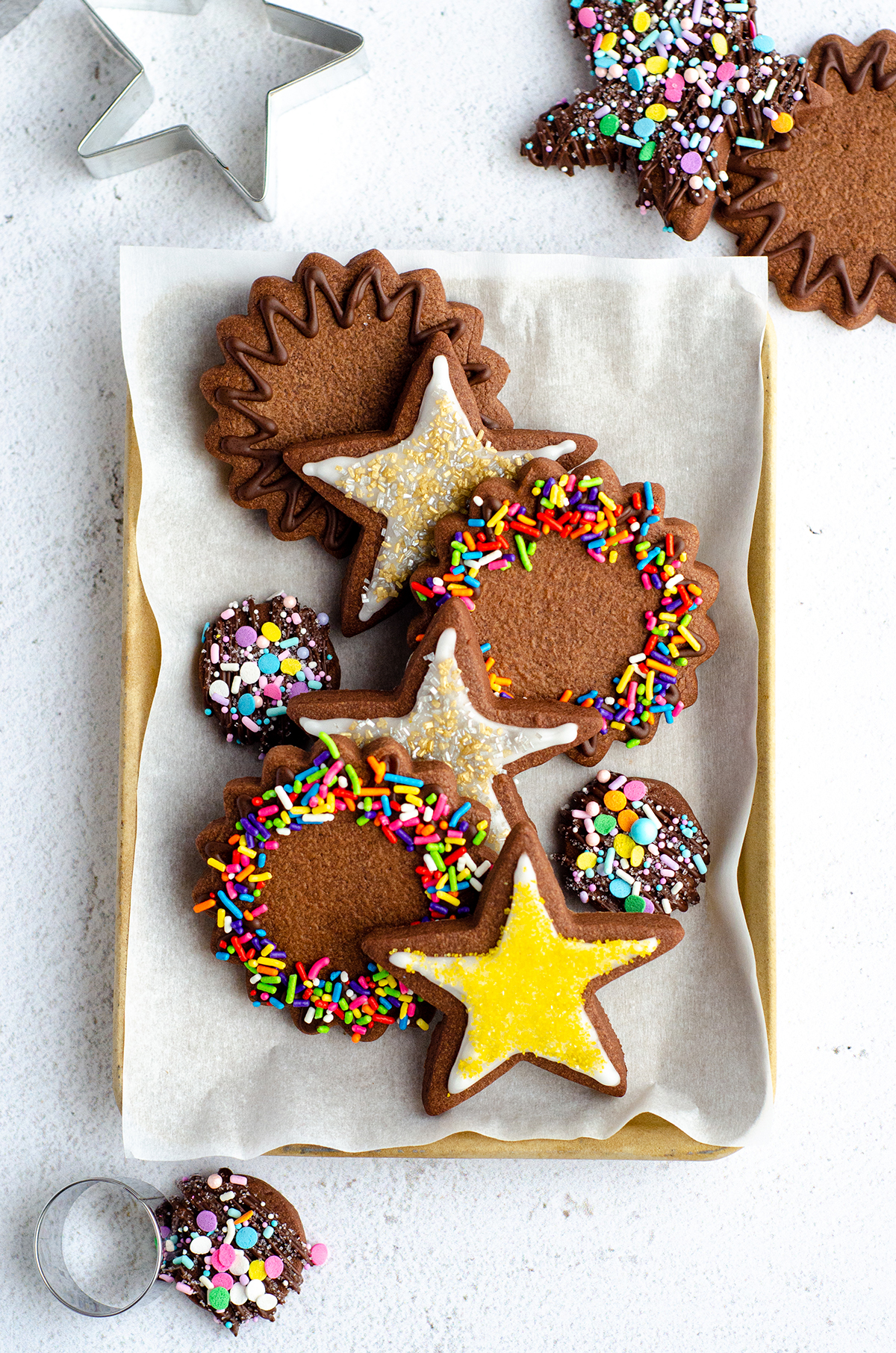 aerial photo of plate of chocolate cut-out sugar cookies decorated with icing and sprinkles