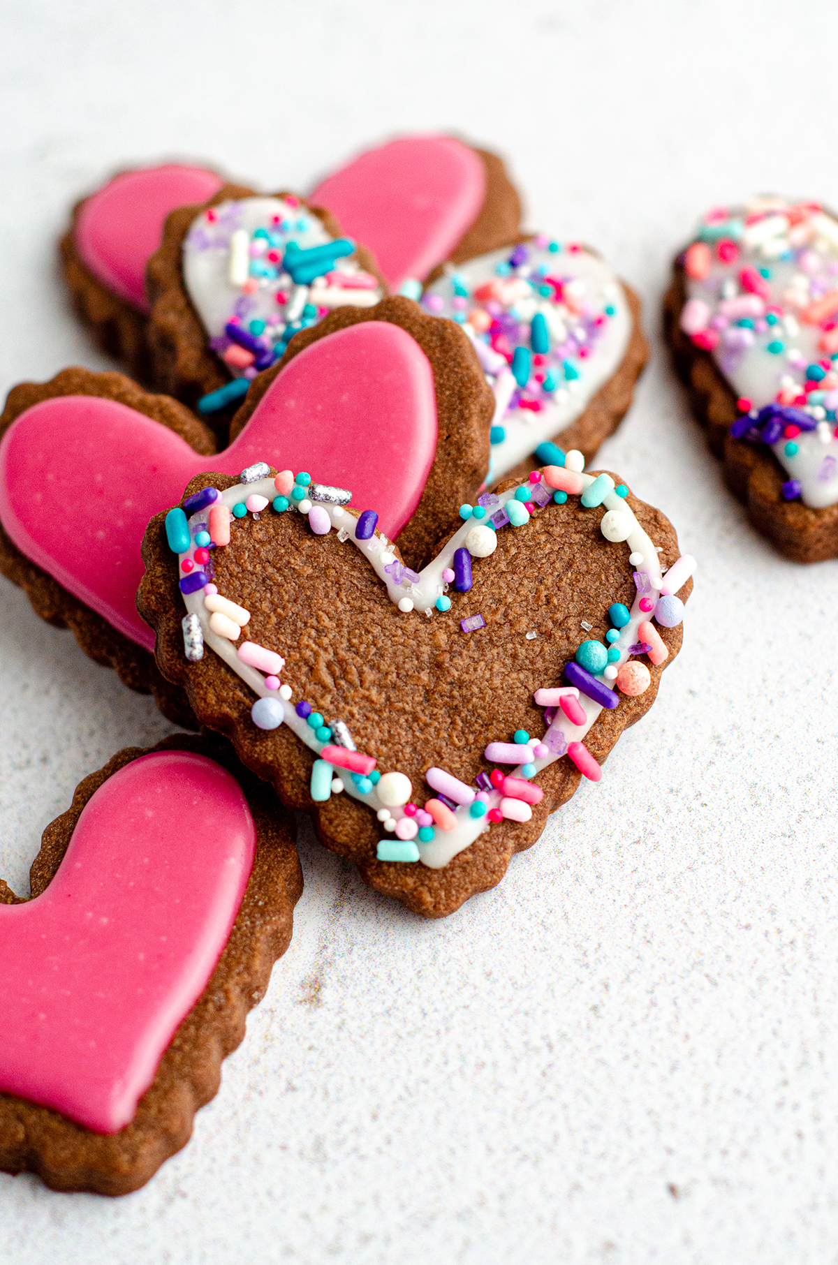 heart shaped chocolate cut-out sugar cookies decorated with icing and sprinkles