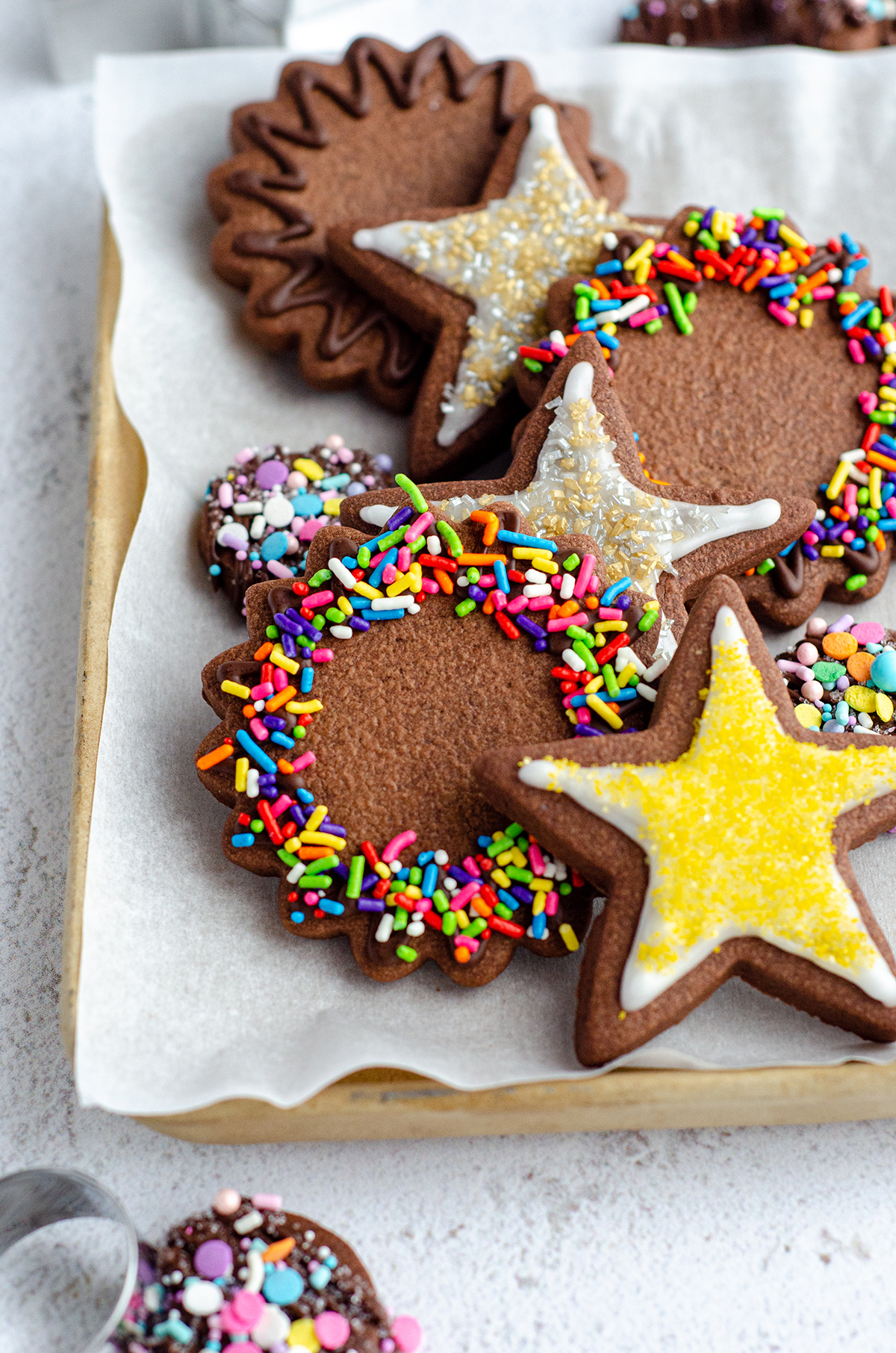plate of chocolate cut-out sugar cookies decorated with icing and spirnkles