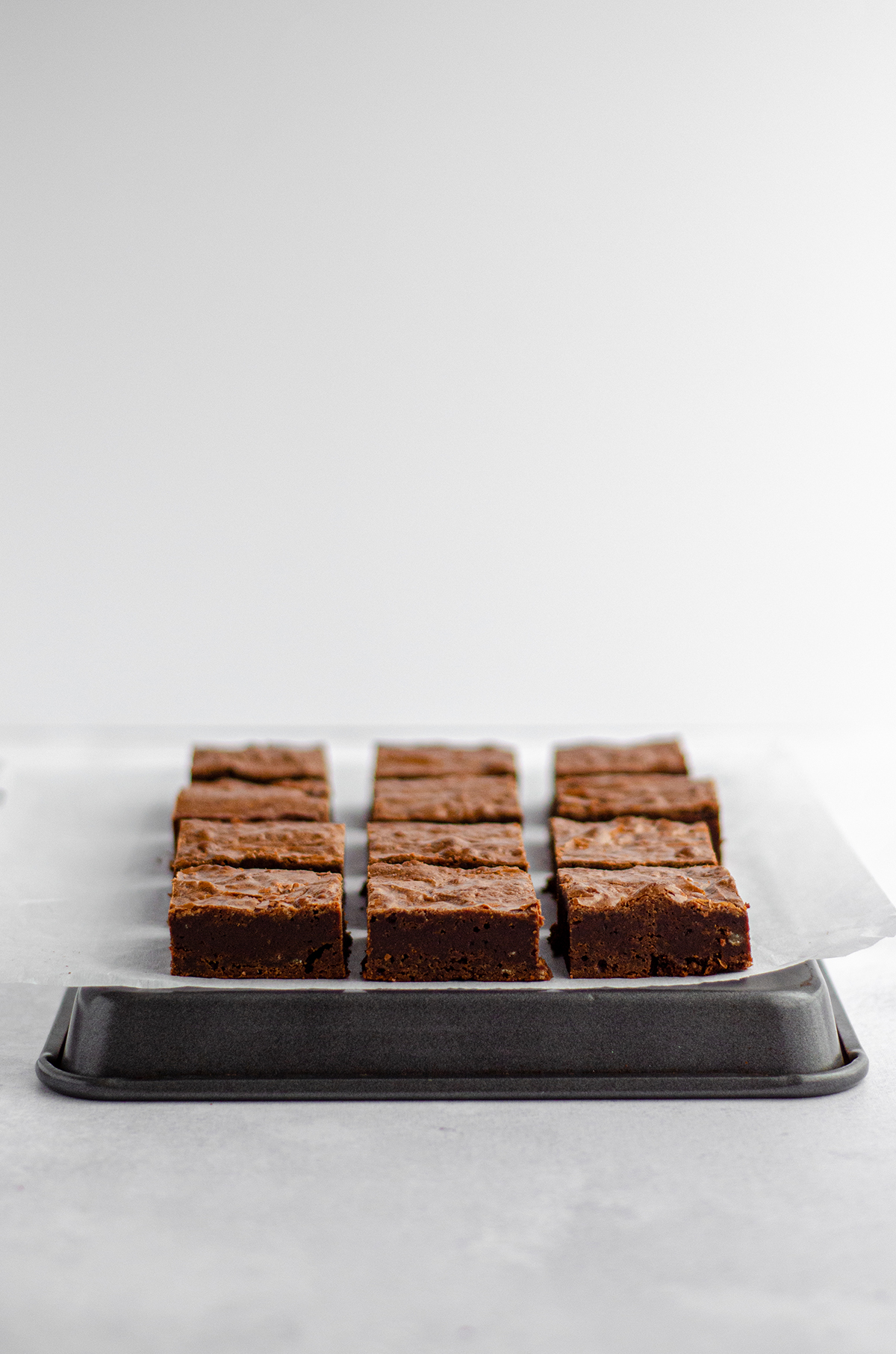 homemade fudgy brownies cut into squares on parchment on a platter