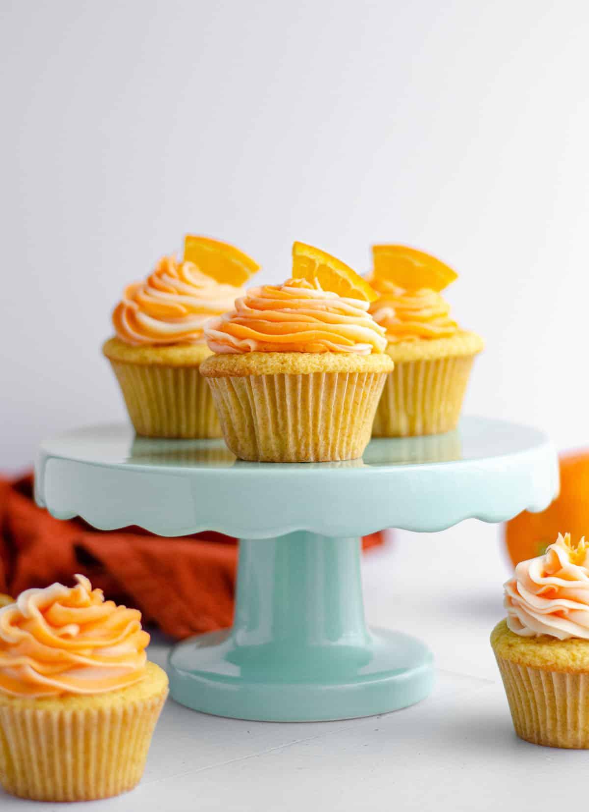 orange creamsicle cupcakes on a light blue cupcake stand