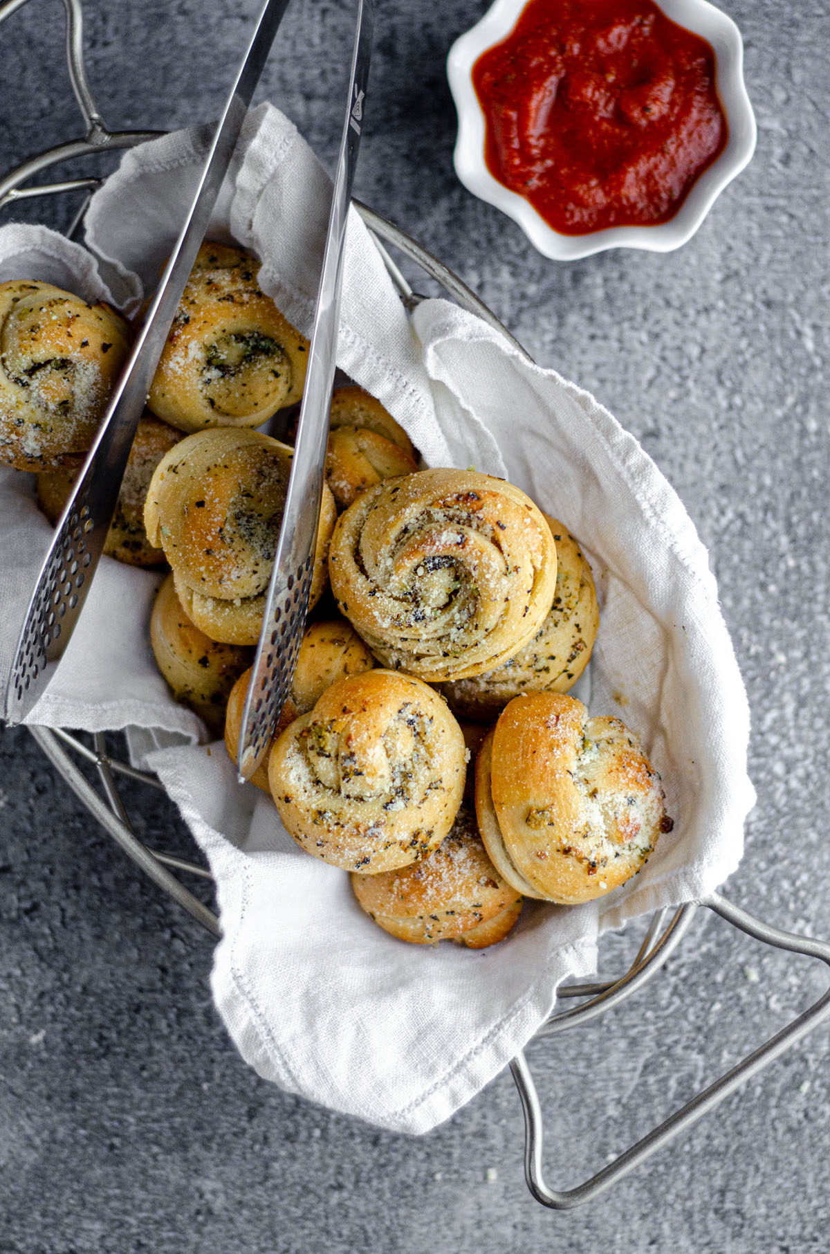 aerial photo of homemade garlic knots in a basket with metal tongs and a cup of marinara