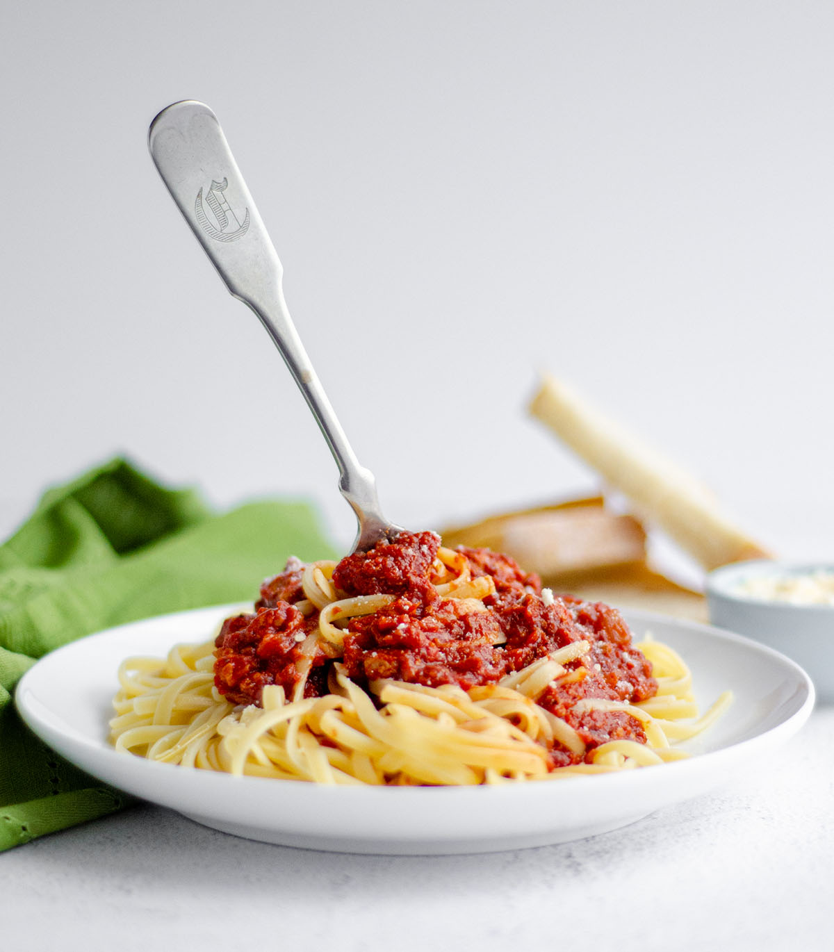 plate of pasta with homemade meat sauce and a fork sticking in the pile of pasta