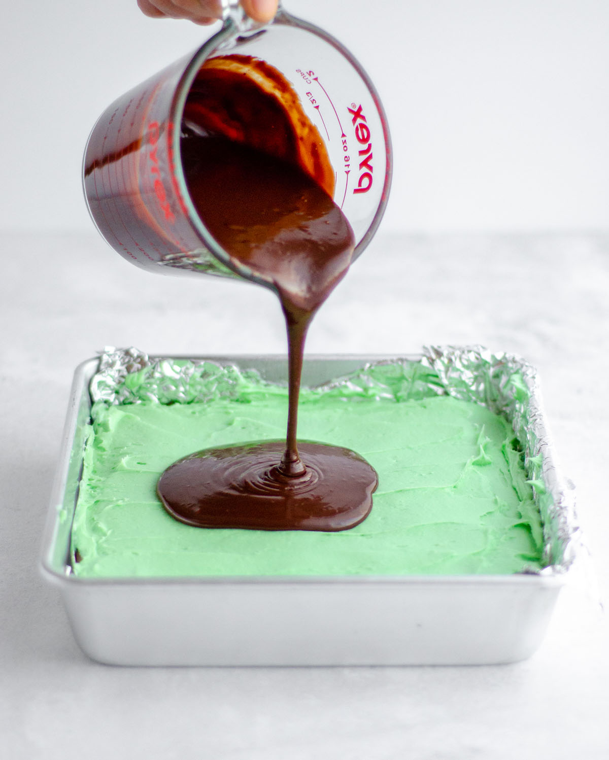 pouring chocolate onto mint layer of mint chocolate brownies