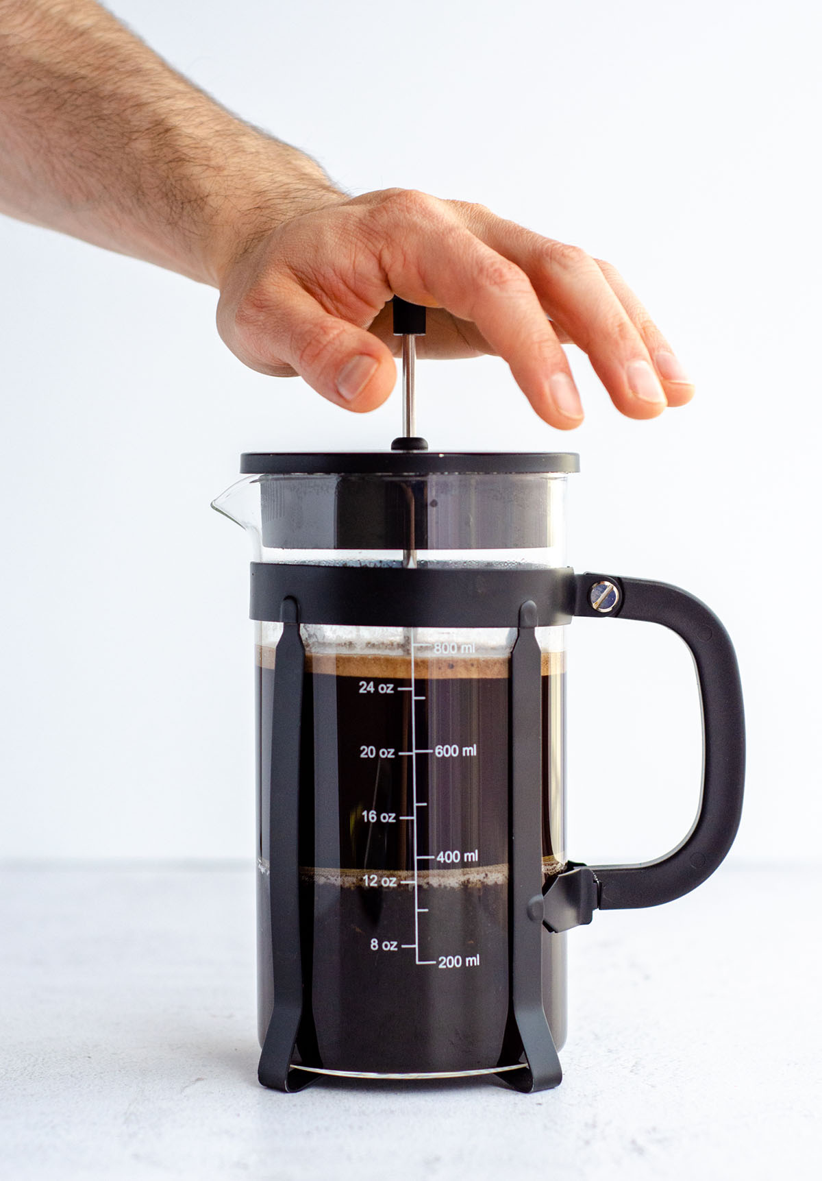 a hand pressing down the plunger on a french press coffee maker