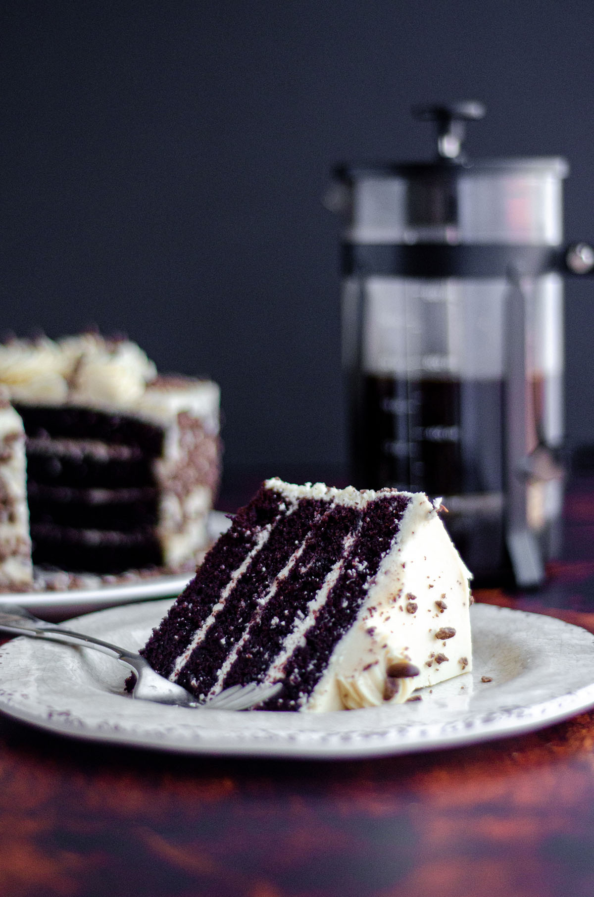 slice of mocha cake with coffee buttercream on a cream colored plate with a fork and a full cake and french press of coffee in the background
