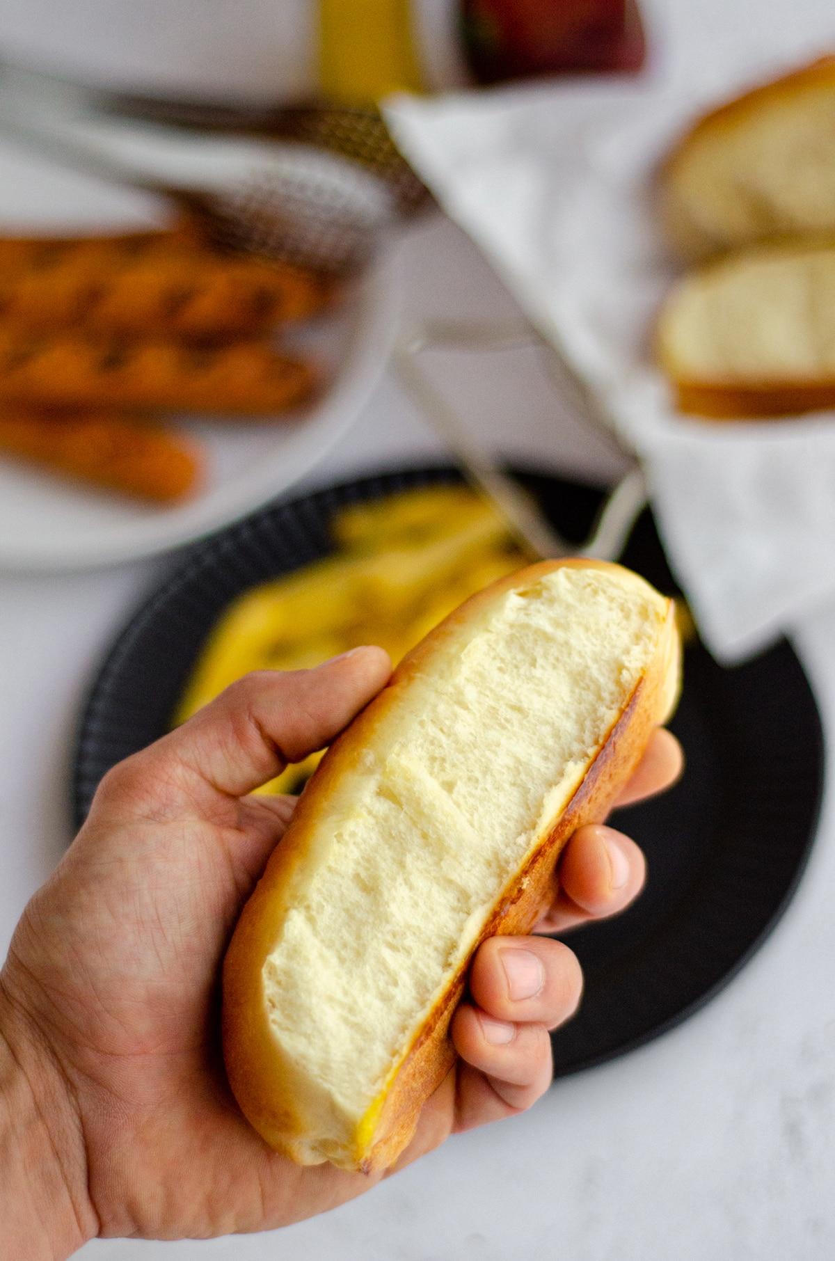 a hand holding a homemade hot dog bun