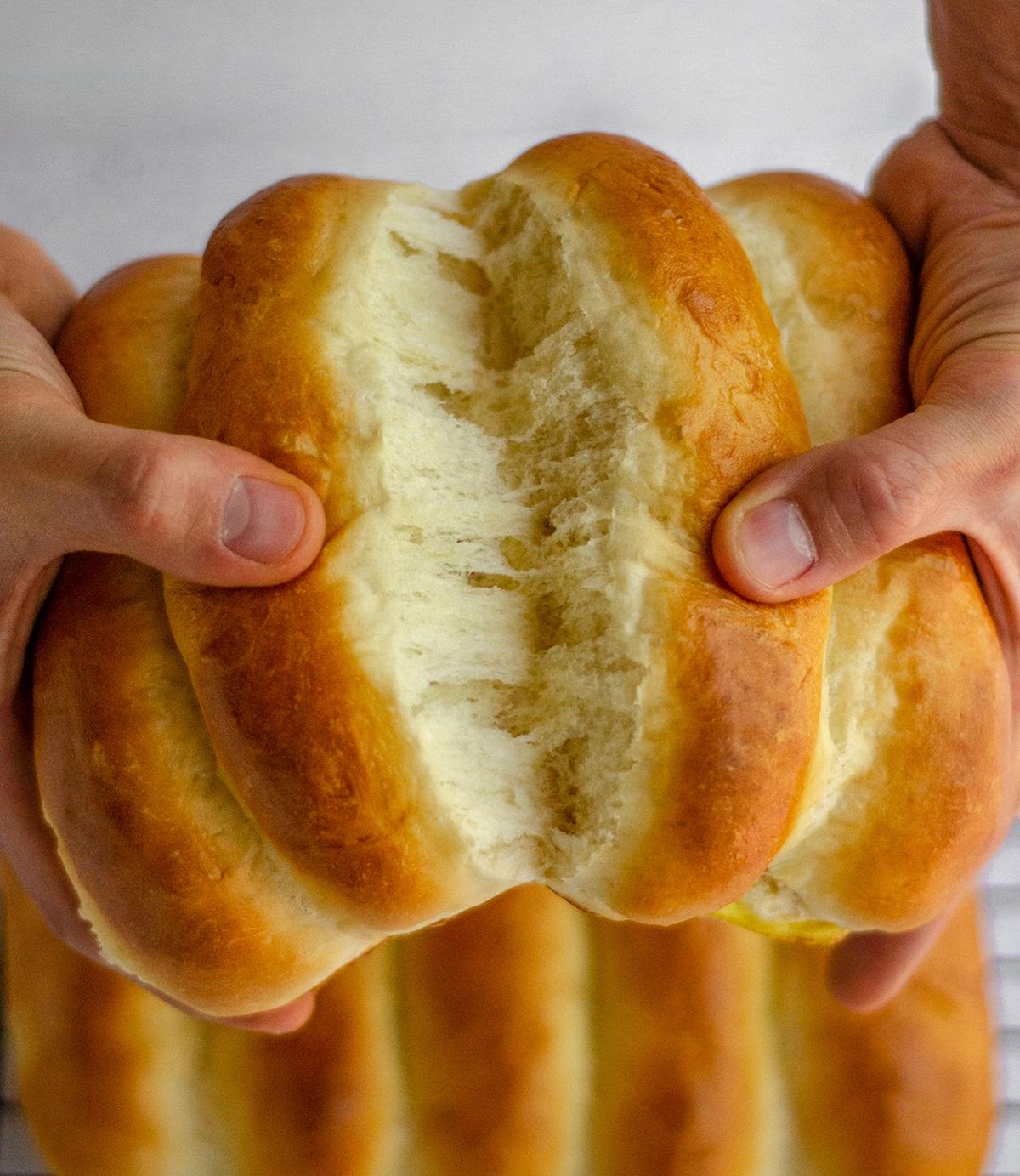 hands pulling apart homemade hot dug buns