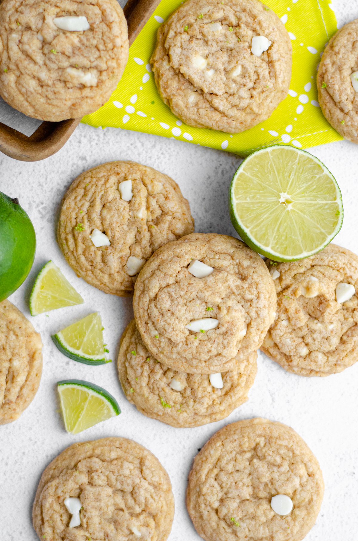 aerial photo of key lime cookies on a white surface with slices of lime around them