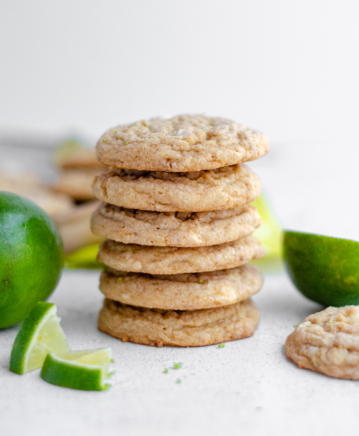 stack of key lime cookies with slices of lime scattered around