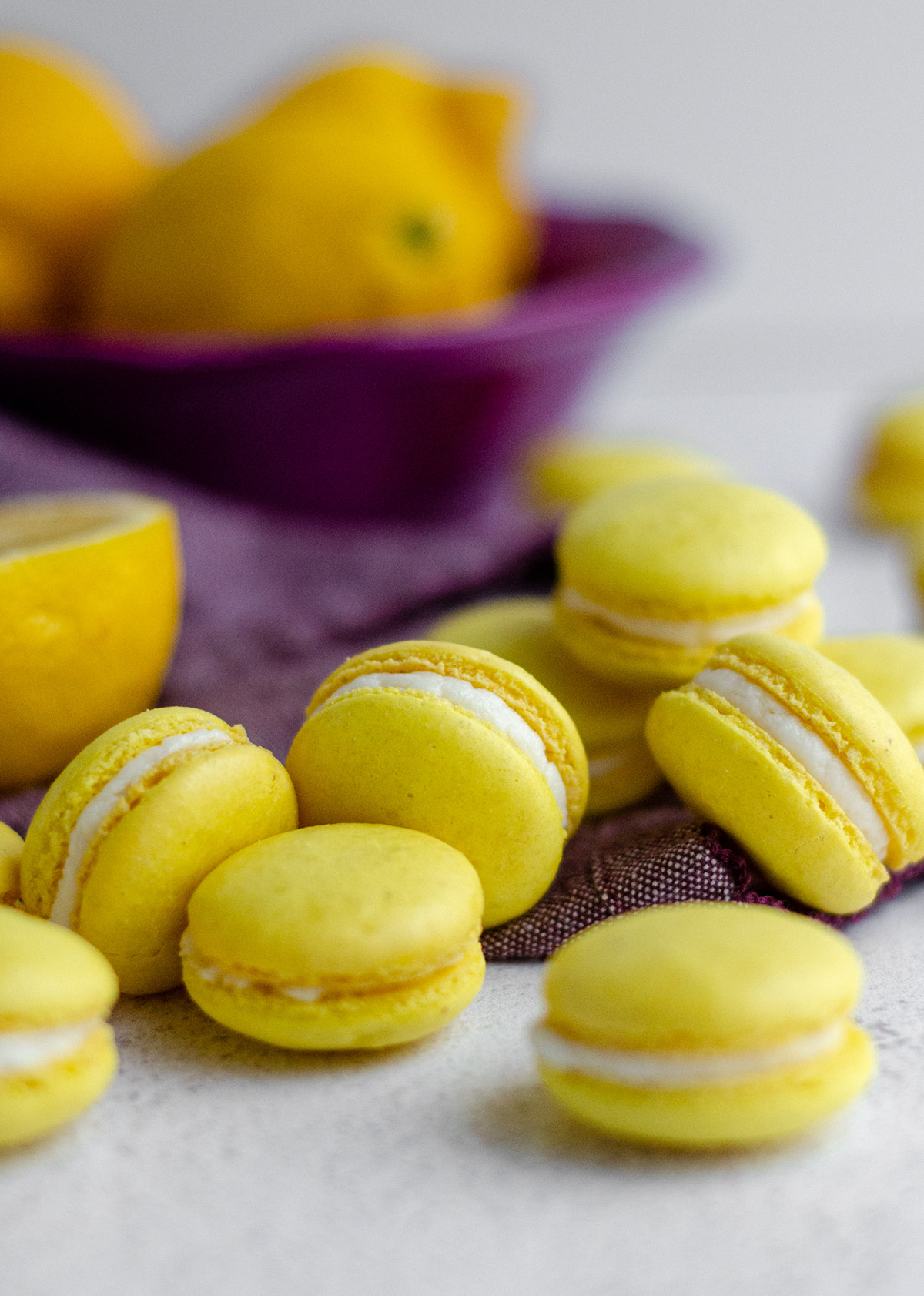 lemon macarons scattered around on a purple kitchen towel