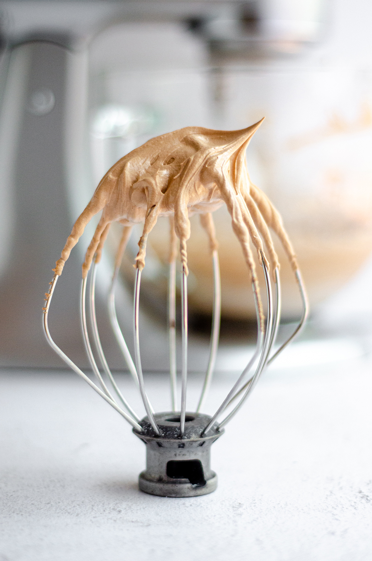 whisk attachment for a stand mixer with chocolate swiss meringue buttercream peaks on the tip