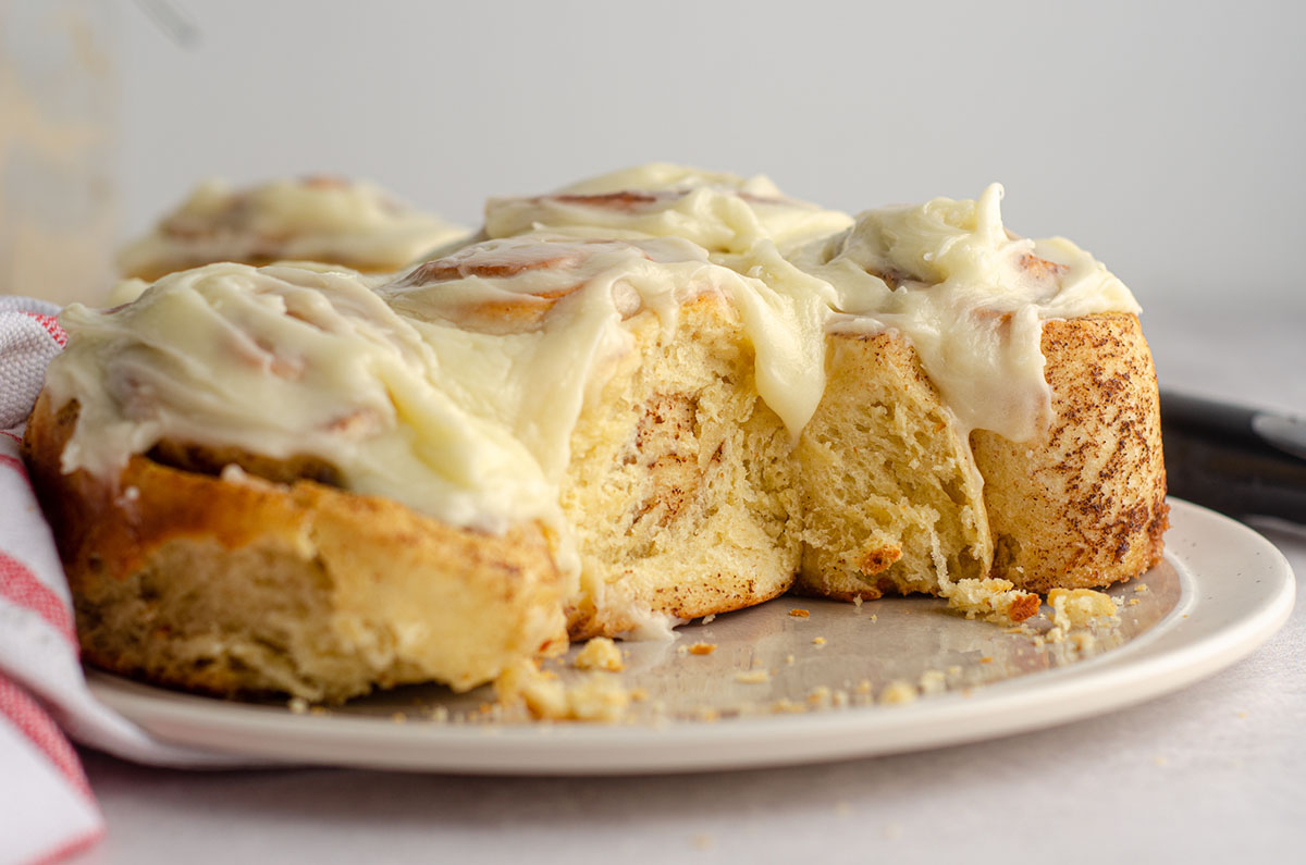 sourdough cinnamon rolls with cream cheese icing on a gray plate