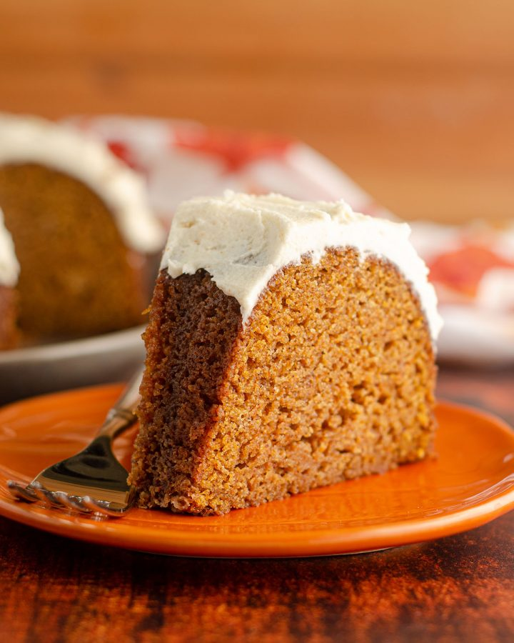 slice pumpkin bundt cake with browned butter buttercream sitting on an orange plate