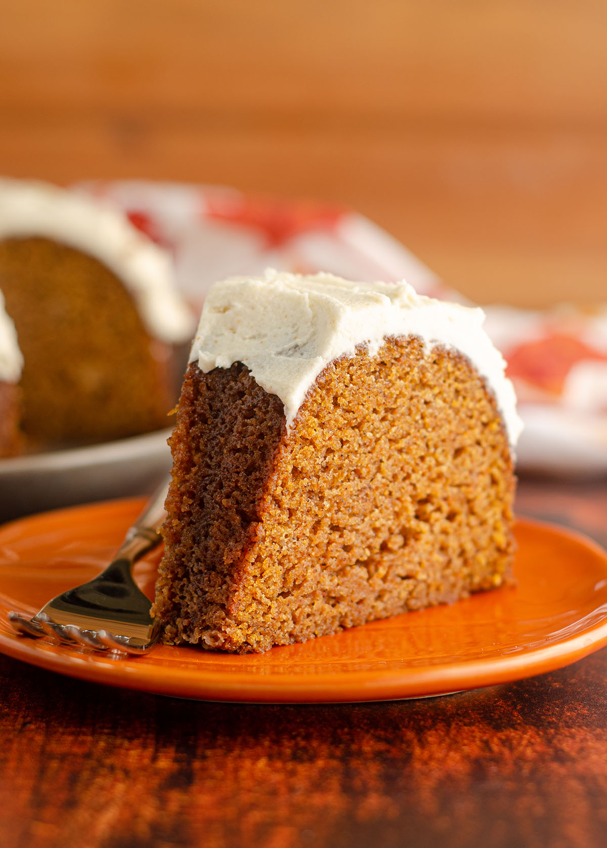 slice of pumpkin bundt cake with browned butter buttercream sitting on an orange plate