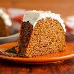 slice pumpkin bundt cake with browned butter buttercream sitting on an orange plate