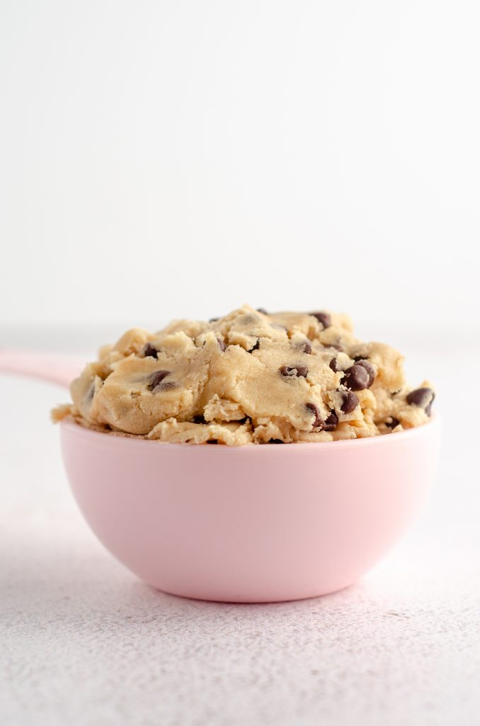 cookie dough in a pink measuring cup