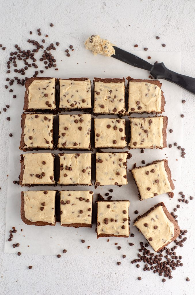 aerial photo of cookie dough brownies with cookie dough buttercream, scattered with mini chocolate chips and a spatula with buttercream on it