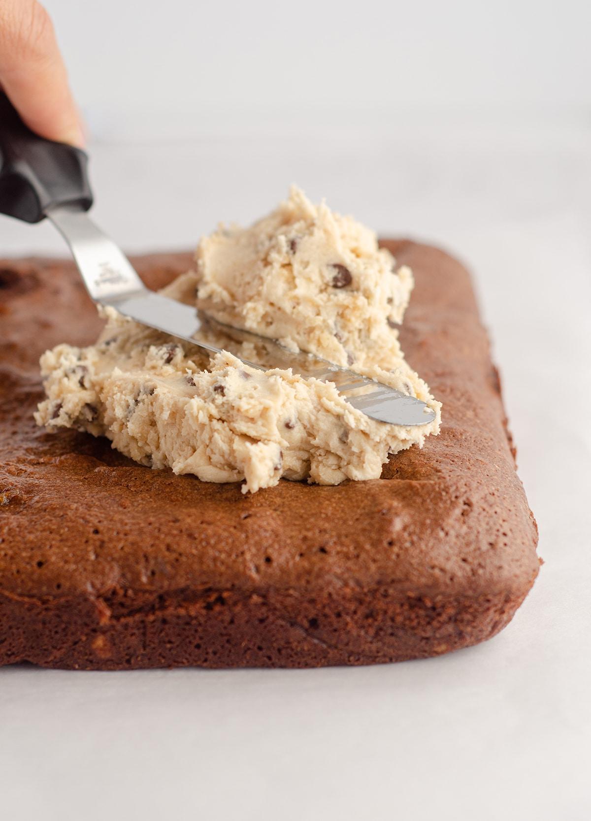 spatula spreading cookie dough buttercream onto brownies