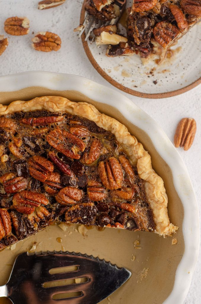 aerial photo of chocolate chip pecan pie with some slices missing and a pie server sitting in the pie plate