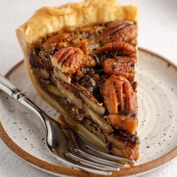 slice of chocolate chip pecan pie sitting on a plate with a fork