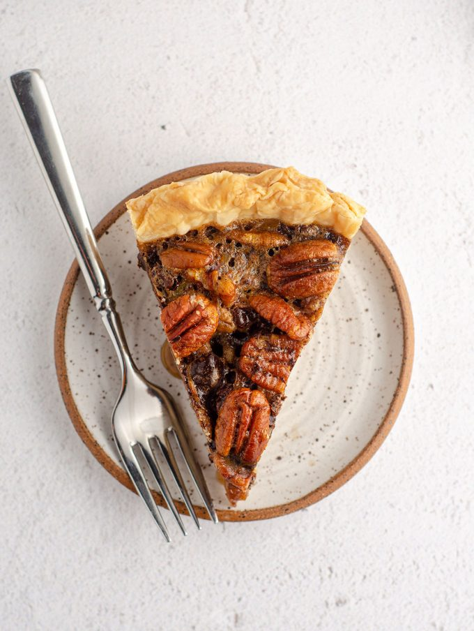 aerial photo of slice of chocolate chip pecan pie sitting on a plate with a fork