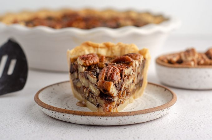 slice of chocolate chip pecan pie sitting on a plate