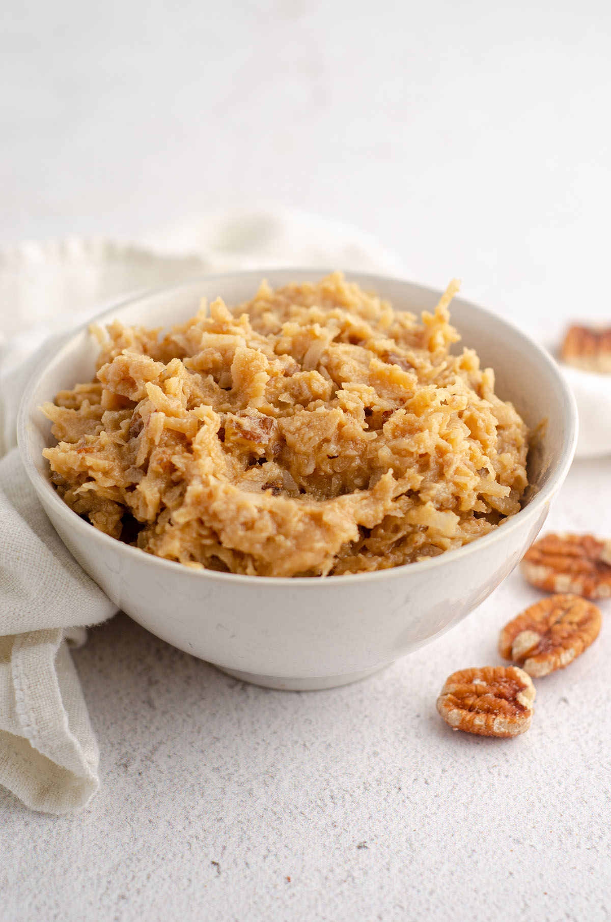 bowl of german chocolate frosting with pecans scattered around bowl