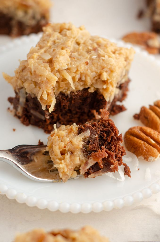 german chocolate brownie sitting on a plate with a fork full of a bite of the brownie