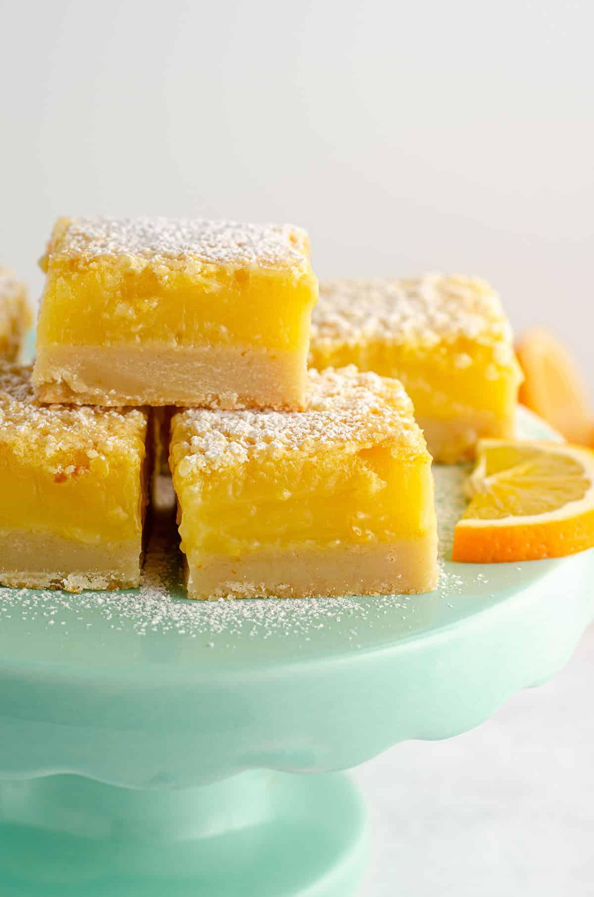 meyer lemon bars sitting on an aqua cake stand